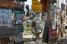 Signpost Forest, Watson Lake, Yukon.  In this photo there are: The number 6 by itself, a white cross, XTASY, and 2012.