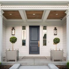 I love the classic porch columns and the charcoal gray front door. Did you notice that ceiling? Incredible! See more on #interiors on the blog today! Design by @foxgroupconstruction . #porch #hallwaysandentrys #frontporch #ighomes #homeexteriors #homebunch