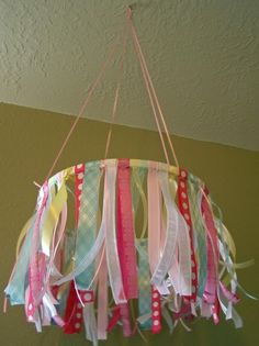 You could also make this thre tiered; each hoop being smaller than the one above and hang them with the smallest one below...use bright colored fabric or strips of poster board.  You could glue pretty wrapping paper ( foil?) to the poster board. before cutting.