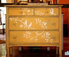 Mustard color painted chest of drawers with stenciling