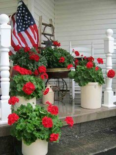 Lovely choice of plants in crocks with the American flag for a patriotic arrangement on a porch