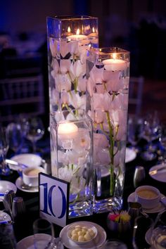 Rent three different size vases and fill with silk orchids and floating candles for easy, simple DIY wedding centerpiece love it but with mason jars and Lilly's maybe :) Simple Wedding Centerpieces, Candle Centerpieces, Wedding Flower Arrangements, Wedding Decorations, Centerpiece Ideas, Vase Ideas, Centerpiece Flowers, Centrepieces, Anniversary Centerpieces