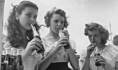 Three young ladies sipping Coca Colas.