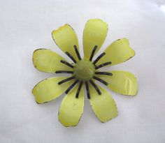 Pale yellow enamel flower pin brooch with green center and black accents