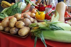 A range of fruit and vegatables on display including sweetcorn, potatoes, peppers and bananas.