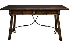 19th Century Antique Spanish Walnut Table - Hand-carved Spanish walnut library table with a thick top above two drawers with iron pulls. The trestle base is joined by iron stretchers with ornate detail.