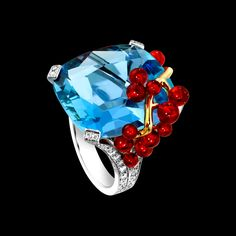 "Piaget Limelight ""Blue Lagoon"" Cocktail Inspiration Ring in 18K white gold set with a cushion-cut aquamarine (approx. 28.03 ct), 13 brilliant-cut fire opals (approx. 3.18 ct) and 58 brilliant-cut diamonds (approx. 1.36 ct) $84,500"