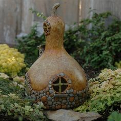 This whimsical gourd shaped cottage is 8 inches high x 5 1/4 inches wide and features a round door and round windows embellished with stone.