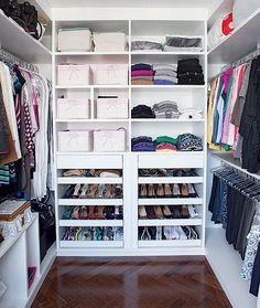 Anexo à suíte principal, o closet rico em divisórias e todo em branco se destaca ainda mais no espaço com piso de madeira cumaru. Projeto das arquitetas Flavia Gerab Tayar e Carina Neves