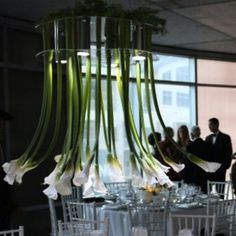 We will be hanging white calla lilies from birch wood to create a floral chandelier that will hang over the dance floor.  It will be square, not round, and will have ivory fabric draped to the ballroom beams framing the dance floor.