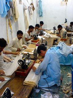 Men making Shalwar Qamiz, Peshawar Old City, Pakistan. Shalwar Qamiz is a long tunic worn over a pair of baggy trousers, usually worn by women, especially in Pakistan. (V)