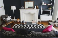 Black and white livingroom in what seems to be an old house. Love the floors and the pink accents.