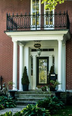 Traditional entrance, wrought iron balcony railing, leaded glass door, topiaries
