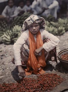 A young vendor at the market in Fort de Kock, Indonesia, poses by her peppers, February 1930.