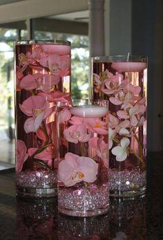 Tubos en cristal bolitas transparentes de cristal al fondo flores blancas más el líquido tiene color rosa!! Velas flotadoras blancas!!