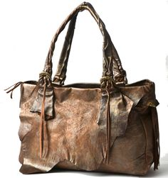 Large zip tote, a naturally imperfect, raw-edged, hand-stitched flap draped over the front. Beneath the flap is a large open, raw-edged pocket with hand-stitched details. Brass leaves scattered the swinging side fringe, 4 leaf-motif buckles,  zip closure
