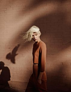 Lightening, shadow, and wind.Ref: Vogue Netherlands July 2014 Fashion magazine Aline Weber Webber Annemarieke Van Drimmelen Photographer beach editorial coat pink camel overalls dungarees