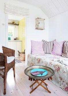 """Den lilla stugan har fått nytt vitlaserat furugolv. Soffbordet, som består av en bricka på en hopfällbar fotpall, kan hängas upp på en krok på väggen. """"Soffan"""", som består av fyra madrasser, blir lätt dubbelsäng – och om alla madrasser sprids ut över golvet får ett helt kompisgäng plats att sova."""