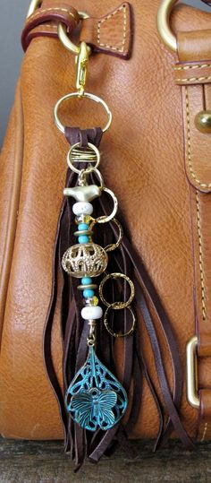 #ThePaintedCabeza ~ This handmade tassel charm can be used on your purse, backpack, zipper, wherever youd like to add some charm! Its made up of dark brown deerskin suede, and different beads - glass, stone, matte gold, and chain. Ive hung a beautifully patinad butterfly charm from it as well. Altogether, the charm is approximately 7.25 long.
