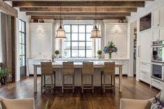 Kitchen with beams and iron windows and doors: PRITCHETT+DIXON