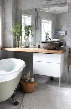 Very natural colours for a grey bathroom, with stone tiles and reclaimed wooden vanity top. Large mirror helps keep it light