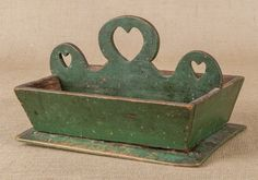 Painted pine knife tray, 19th c., with a heart cutout handle, retaining an old green surface, 7 1/2'' h., 12'' w., 8 3/4'' d.