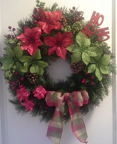 """Christmas Holiday artificial evergreen wreath with red and green poinsettias, pinecones, berries, presents, """"ho ho ho"""" and a bow."""