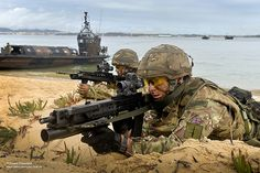 Pictured are two Royal Navy Marines taking part in a simulated beach landing with reinforcements aboard the Land Craft in the background.