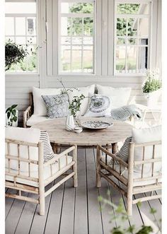 Rustic wood furniture and modern printed pillows combine to give this patio a stylish, yet relaxed ambiance.