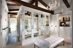 Amazing walk-in closet design with rustic wood beams, white leather tufted bench with bolster pillow and white built-in mirrored cabinet doors.