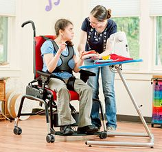 A therapists aids a student using adaptive equipment to practice motor control skills in a classroom setting