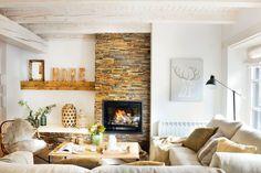 Salón rústico nórdico con chimenea con embocadura de piedra y paredes en blanco