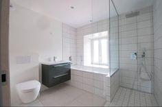Salle de bain blanche avec douche italienne, WC suspendu et baignoire rectangle.