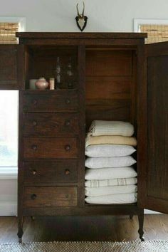 I absolutely need this in my life. Gorgeous dark antique blankets and linens armoire.