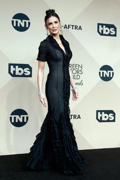 Demi Moore made an unannounced appearance at the Screen Actors Guild Awards on Saturday night, presenting the award foroutstanding performance by a cast in a motion picture.  While delivering the green statue to the Spotlight team, the 53-year-old wore a black Zac Posen gown with sheer stripe detailing