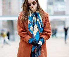 Rust-orange coat worn with a colorful silk scarf
