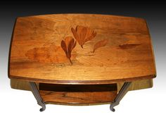 An Emile Galle Art Nouveau two tier occasional table, inlaid with a dragonfly resting on a water lily.The marquetry is made of a combination of rosewood, walnut and fruitwoods. The table is signed: 'Gallé' ;France c.1910.Size:heigth 75cm,    depth 34cm,width 58 cm , NO199 SOLD