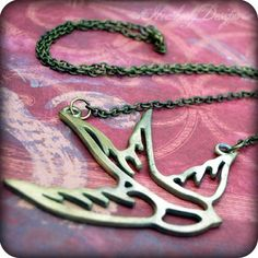 Tattoo: bronze swallow silhouette necklace