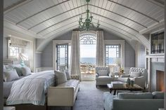 In the master bedroom, a boat-like bow ceiling sits within a dutch gambrel roof. The antique mirror above the fireplace conceals a TV; beyond the expansive Palladian window, a small balcony faces the ocean. My dream bedroom 😍 Dream Master Bedroom, Home Bedroom, Bedroom Decor, Bedroom Ideas, Bedroom Interiors, Bedroom Designs, Bedroom Lighting, Girls Bedroom, Beach House Interiors