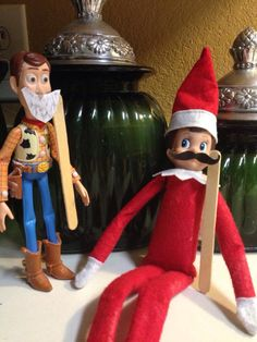 Elf on a shelf - mustache Printed out a mustache & beard and used double sided adhesive to glue to Popsicle stick and then used double sided adhesive to temporarily tape to face of elf and woody.