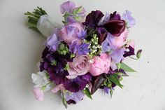 "A beautiful early summer wedding bouquet of Pink ""Sarah Bernhardt"" Peonies, Deep Purple/Aubergine Calla lilies, Memory Lane Roses, Sweet Scented Lilac, White, Pink and Deep Purple Sweet Peas, Brodea, Lisianthus, Alchemilla Mollis, Deep purple Lissianthus and fresh fragrant Lily of the Valley"