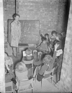 1941 A teacher and her pupils have a lesson in a basement at Greek Road School in South East London. Although many schools were evacuated during the war, many chose to stay and 'make the best of it', converting cellars and basements into makeshift classrooms.