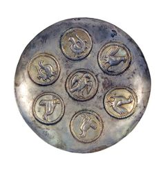 Persian silver plate with traces of gold wash decorated with seven standing birds including roosters and an eagle to the center, framed in a ridged circular design, 500 BC.