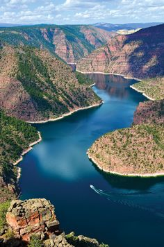 A boat cruises along the winding contours of the pristine landscape of Red Rock Canyon in Flaming Gorge, Utah.