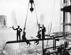 Two waiters serve two steel workers lunch, on a girder high above New York City, 14th November 1930.
