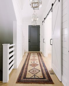 White Modern Farmhouse hallway features bleached hardwood floors, shiplap paneling, vintage kilim runner, grey interior door and Visual Comfort Suzanne Kasler Morris lanterns. Farmhouse Interior Doors, Grey Interior Doors, Modern Farmhouse Interiors, Modern Interior, Interior Door Styles, Grey Interiors, Rustic Farmhouse, Decor Interior Design, Interior Decorating
