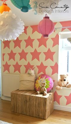 """""""Mermaid Cottage"""" a sweet girls room makeover for two sisters! On the rear wall we designed a star template and painted pale bubblegum pink stars. We added a bamboo dress-up chest and lots of hanging lanterns & tissue paper pom poms"""