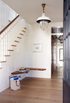A custom-built bench constructed from live-edge planks floats on the wall in the foyer, nodding to this New Jersey getaway's nautical surroundings. - Photo: Laura Moss / Design: Barbara Bottinelli