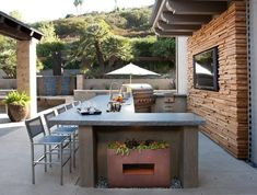U shaped outdoor kitchen boasts concrete countertops fitted with a sink with polished nickel gooseneck faucet and a stainless steel barbecue.