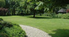 Rodenburg Tuinen: Villatuin met Schellevis of oud hollandse tegels antraciet, Buxuswolken, grote tuintafel in teakhout, potten met agapanthus